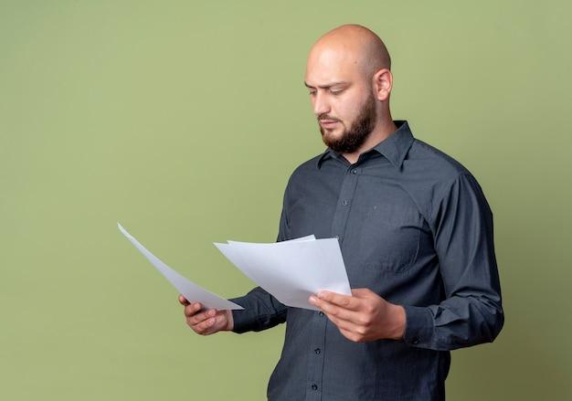 집중된 젊은 대머리 콜 센터 남자 보유 및 올리브 그린에 고립 된 문서보고