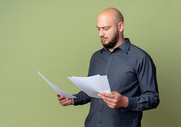 Concentrated young bald call center man holding and looking at documents isolated on olive green