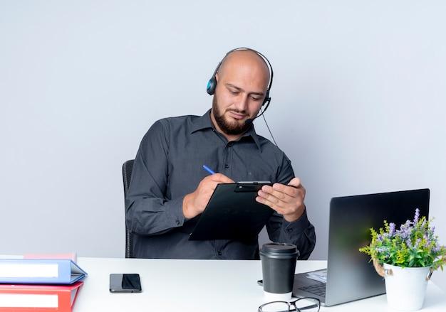 Concentrato giovane uomo calvo call center che indossa la cuffia avricolare seduto alla scrivania con strumenti di lavoro scrivendo con la penna negli appunti isolato su bianco