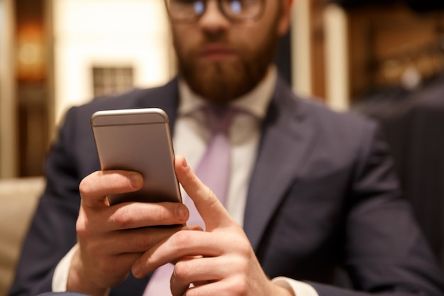 Concentrated young bearded businessman chatting by phone