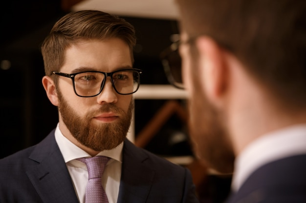 Concentrated young bearded businessman looking at mirror