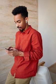 携帯電話を持って画面を注意深く見て、赤いシャツを着て家のインテリアにポーズをとって、集中した若いひげを生やした暗い肌のブルネットの男
