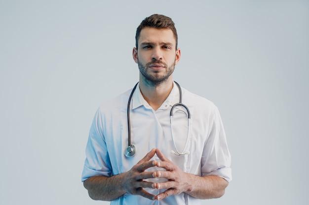 Сосредоточенный молодой бородатый европейский мужской портрет доктора. человек в белом халате со стетоскопом. изолированные на сером фоне с бирюзовым светом. студийная съемка. скопируйте пространство.