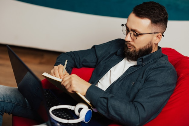 Сосредоточенный молодой бородатый мужчина в повседневной одежде и очках использует ноутбук для заметок в блокноте, сидя в гостиной дома.