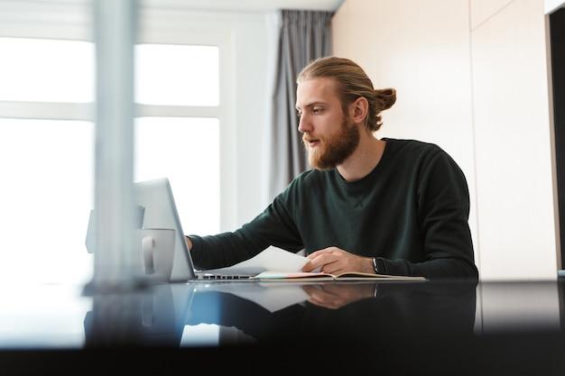 Сосредоточенный молодой бородатый человек, сидящий дома с помощью портативного компьютера, работает с документами.