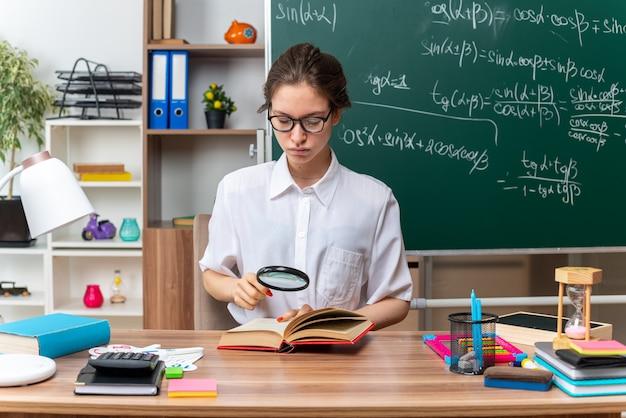 Concentrato giovane insegnante di matematica femminile bionda con gli occhiali seduto alla scrivania con strumenti scolastici guardando il libro aperto attraverso la lente di ingrandimento in classe