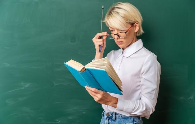Concentrato giovane insegnante di sesso femminile bionda con gli occhiali in aula in piedi nella vista di profilo davanti alla lavagna che tiene il bastone del puntatore e legge il libro che afferra gli occhiali con lo spazio della copia