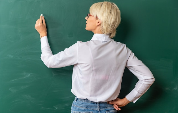 Concentrated young blonde female teacher wearing glasses in classroom standing in behind view in front of chalkboard writing on chalkboard with chalk keeping hand on waist