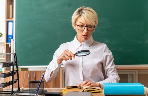 Концентрированная молодая блондинка учительница в очках сидит за столом со школьными принадлежностями в классе, глядя на открытую книгу через увеличительное стекло