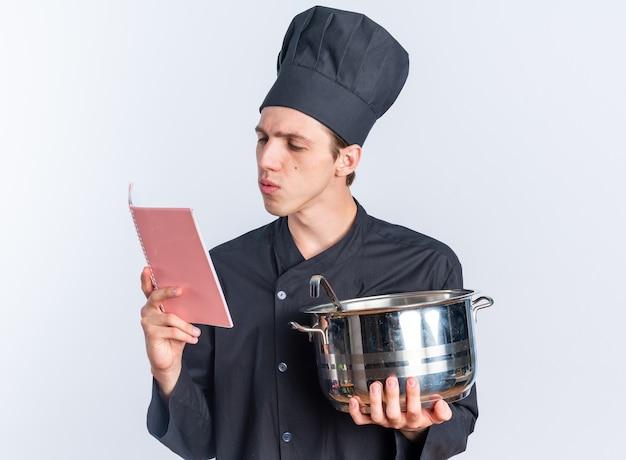 Сосредоточенный молодой блондин мужчина-повар в униформе шеф-повара и кепке держит блокнот для чтения с горшком