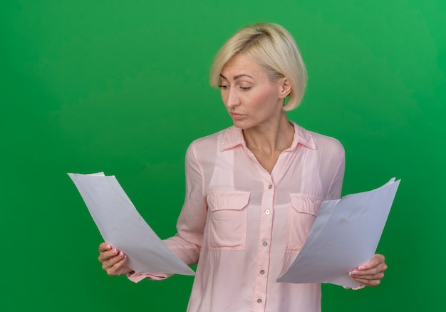 Concentrated young blonde slavic woman holding and looking at documents isolated on green background