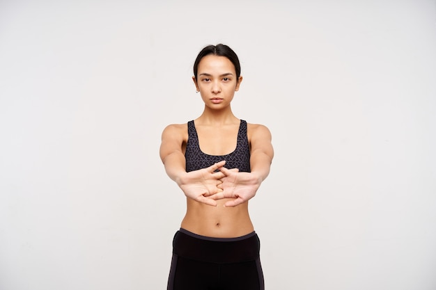Concentrated young brown-eyed sporty female with casual hairstyle crossing her fingers while stretching hands, doing morning workout while standing over white wall