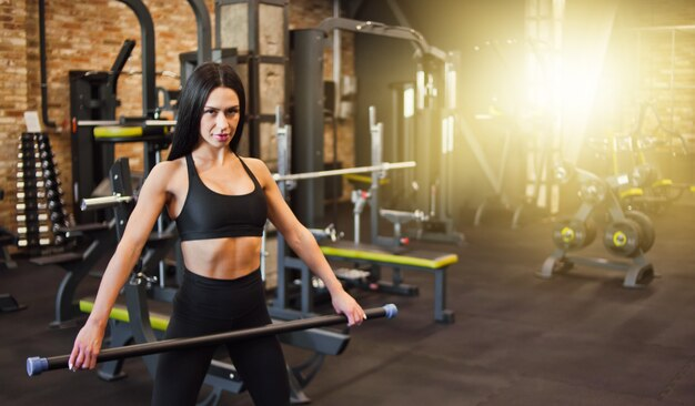 체육관에서 그녀의 손에 바디 바 체조 운동을하는 sportwear에 집중된 젊은 갈색 머리