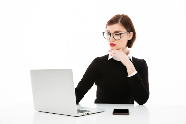 Concentrated young business lady using laptop computer.