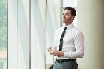 窓を見て、集中した若いビジネスマン