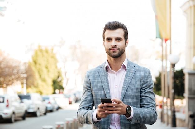 Giovane uomo d'affari concentrato all'aperto che chiacchiera Foto Gratuite