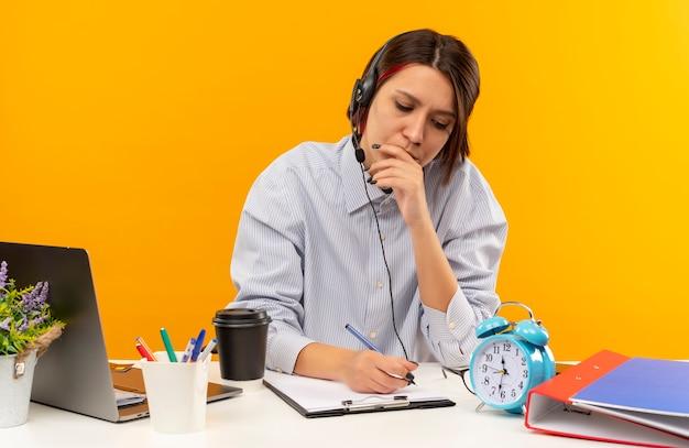 Концентрированная молодая девушка из колл-центра в наушниках сидит за столом, кладет руку на рот и пишет, изолированные на оранжевом