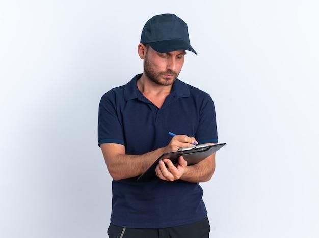 Concentrato giovane fattorino caucasico in uniforme blu e cappuccio che scrive con penna su appunti isolato su muro bianco con spazio di copia