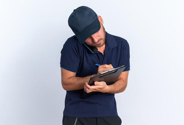 파란색 유니폼을 입은 백인 배달원에 집중하고 복사 공간이 있는 흰색 벽에 펜으로 클립보드에 전화로 글을 쓰는 모자를 쓰고 있습니다.