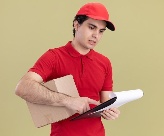 赤い制服とキャップを保持しているカードボックスの脇の下とクリップボードを保持しているクリップボードの人差し指を見て集中している若い白人配達人