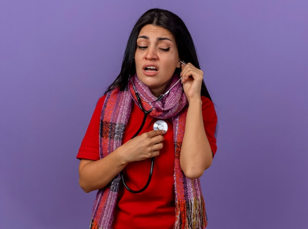 コピースペースで紫色の壁に分離された彼女の心拍を聞いて横を見てスカーフと聴診器を身に着けている集中した若い白人の病気の女の子