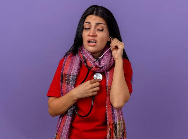 Sciarpa da portare della giovane ragazza ammalata caucasica concentrata e stetoscopio che esamina lato che ascolta il suo battito cardiaco isolato sulla parete viola con lo spazio della copia