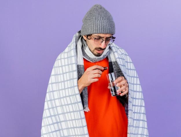 Concentrato giovane indoeuropeo uomo malato con gli occhiali inverno cappello e sciarpa avvolto in plaid versando medicamento in vetro in bicchiere d'acqua isolato sulla parete viola con spazio di copia