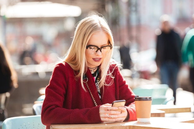 Concentrated young caucasian lady sitting in cafe