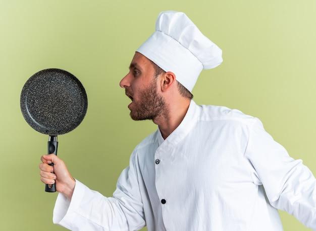 Сосредоточенный молодой кавказский повар в униформе шеф-повара и кепке, стоящий в профиле, держит сковороду и смотрит в сторону, изолированную на оливково-зеленой стене