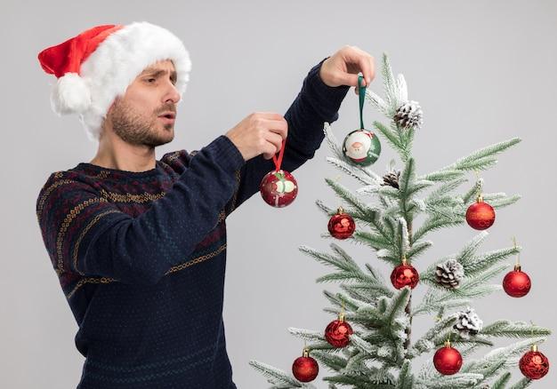Concentrato giovane uomo caucasico che indossa il cappello di natale in piedi vicino all'albero di natale decorandolo con palline di ornamento di natale isolato sul muro bianco