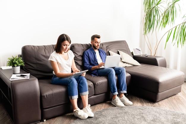 Сосредоточенная молодая пара в повседневной одежде сидит на удобном диване и использует устройства во время работы фрилансером дома
