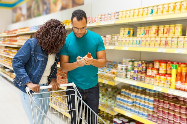Concentrated young couple standing near shelves with canned goods