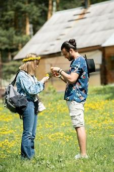 Сосредоточенная молодая пара гуляет по полю одуванчиков и вместе плетет венок