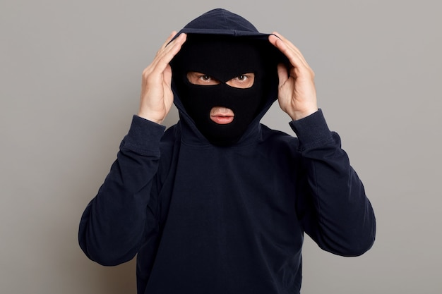 Concentrated young criminal man in a bandit mask dressing a hood