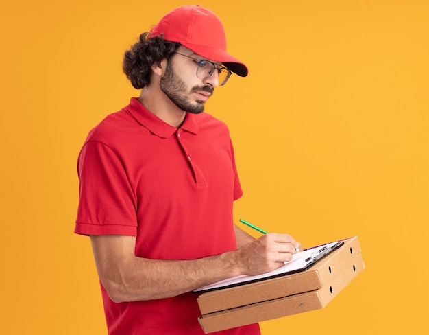 Concentrato giovane fattorino in uniforme rossa e berretto con gli occhiali in piedi nella vista di profilo che tiene i pacchetti di pizza che scrivono sugli appunti con la matita isolata sulla parete arancione