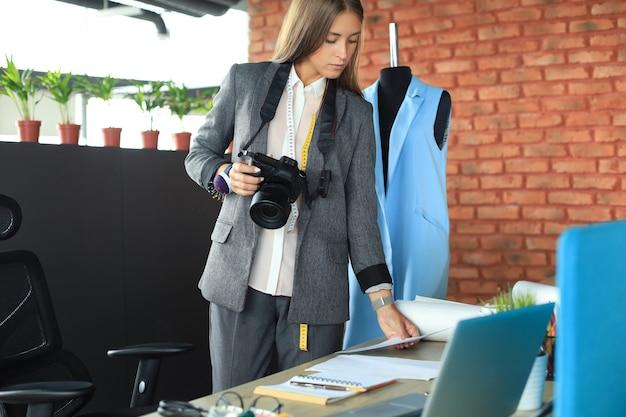 Сосредоточенный молодой дизайнер использует цифровую камеру, стоя возле стола в своем творческом офисе.