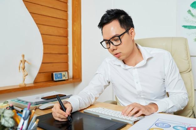 顧客のロゴタイプを描くときにデジタルペンとグラフィックタブレットを使用して集中した若いデザイナー