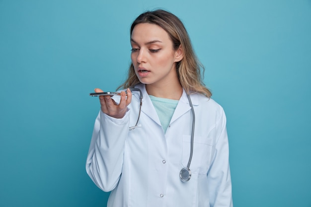 의료 가운과 청진기를 착용하고 목을 잡고 마이크로 이야기하는 휴대 전화를보고 집중된 젊은 여성 의사