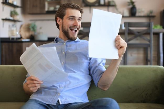 Сосредоточенный молодой внештатный бизнесмен сидит на диване с ноутбуком и рассматривает документы.