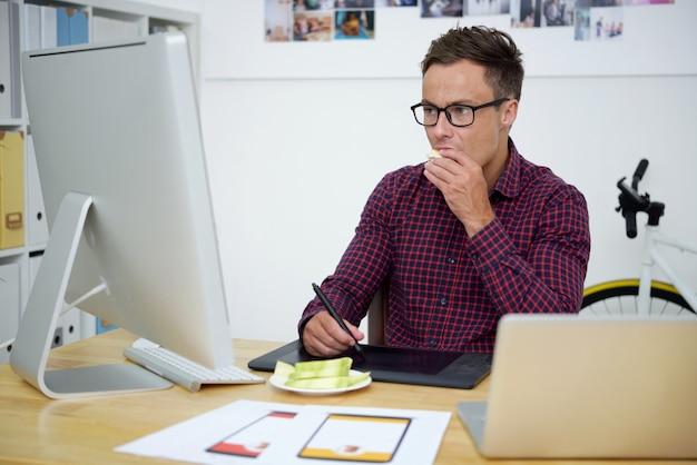 Сосредоточенный молодой графический дизайнер работает за компьютером и ест нарезанные фрукты за своим офисным столом