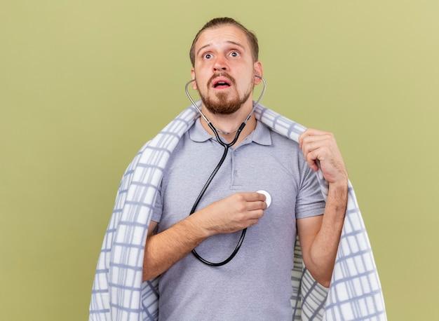 聴診器を身に着けている集中した若いハンサムなスラブの病気の人は、コピースペースのあるオリーブグリーンの壁に孤立して見上げる格子縞をつかむ格子縞に包まれた彼自身の心拍を聞いています