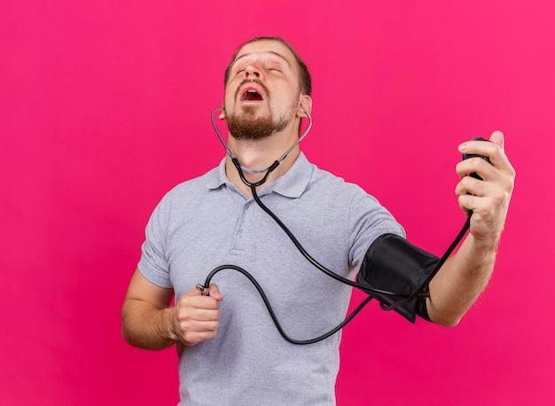 Сосредоточенный молодой красивый славянский больной мужчина со стетоскопом, измеряющий его давление с помощью сфигмоманометра с закрытыми глазами, изолирован на розовой стене с копией пространства