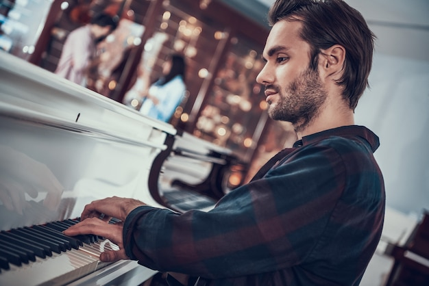 Concentrated young hipster plays piano