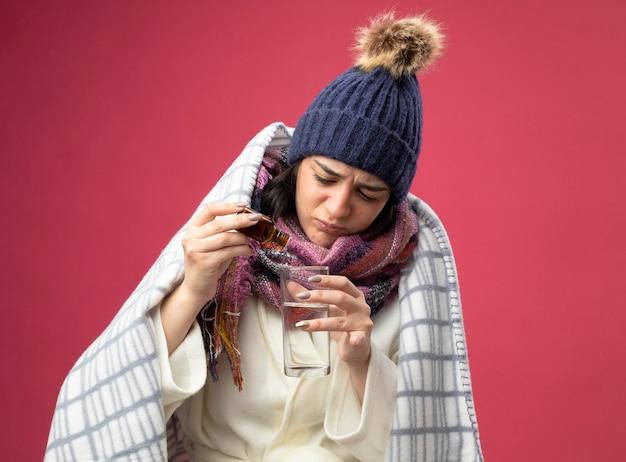 Сосредоточенная молодая больная женщина в халате, зимней шапке и шарфе, завернутом в плед, добавляя лекарство в стакан с водой, изолированный на розовой стене