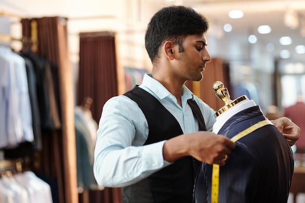 巻尺でオーダーメイドのジャケットの肩を測定する集中した若いインドのテーラー