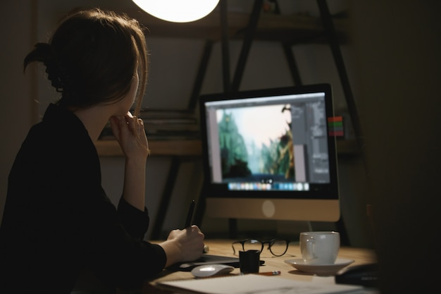 밤에 컴퓨터를 사용하여 집중된 젊은 아가씨 디자이너