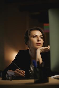 Концентрированный молодой леди дизайнер сидит в офисе ночью
