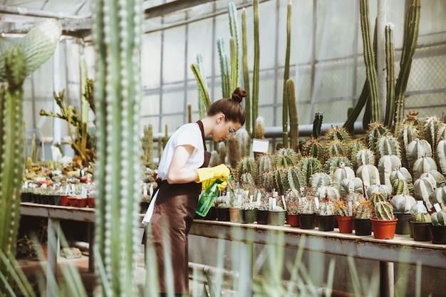 Giovane signora concentrata in vetri che stanno nella serra
