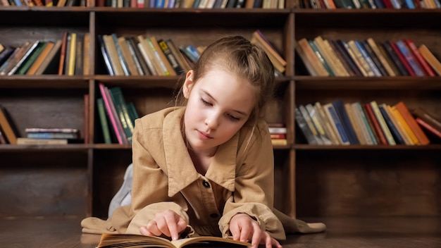 집중된 젊은 여성은 코로나바이러스 전염병 격리에서 책장에 대항하여 나무 탁자에서 온라인 수업을 준비하는 책을 읽습니다