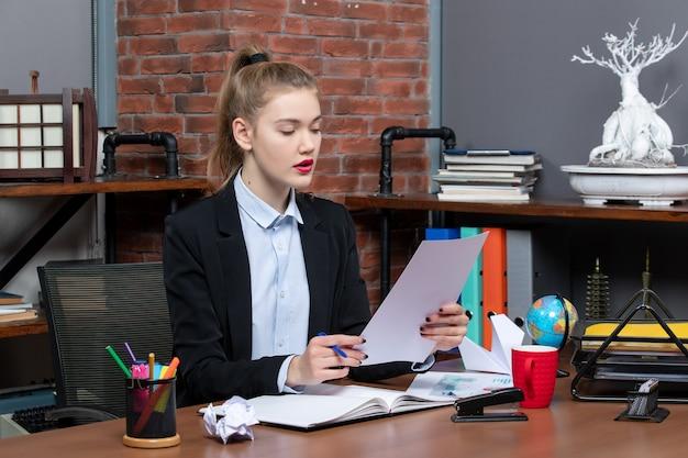 집중된 젊은 여성이 테이블에 앉아 사무실에서 공책에 있는 메모를 읽고 있습니다.